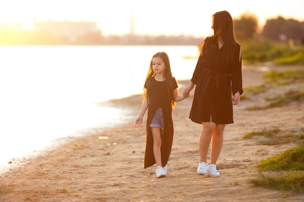 Young mother and daughter playing and walking on sandy beach
