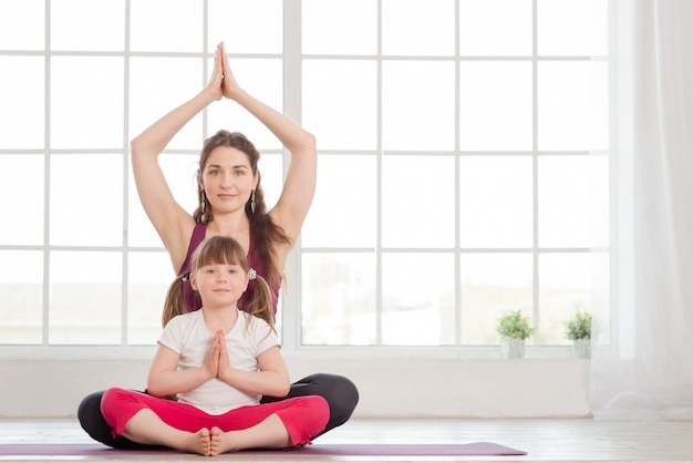 Young mother and daughter sitting in lotus position