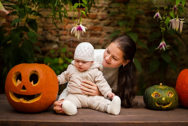 Young mother and daughter sitting near pumpkins, halloween eve
