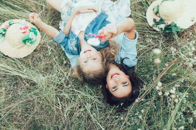 The young mother and daughter with candies on green grass