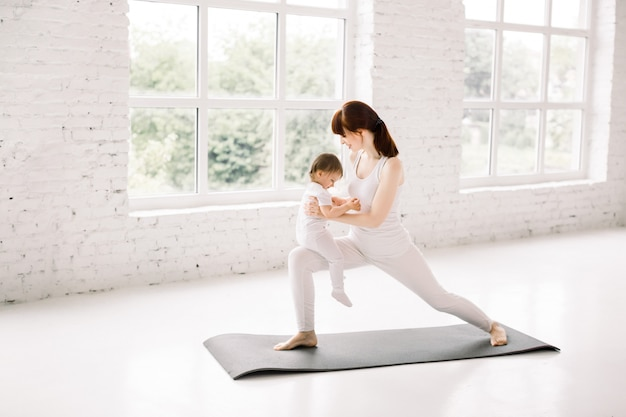 Young mother doing yoga, lunges, with her little baby at big light gym hall