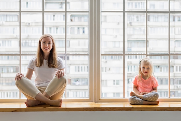 Young mother doing yoga with 3-years daughter in front of window. happy mom smiling while practicing yoga together with her cute girl sitting in lotus pose asana