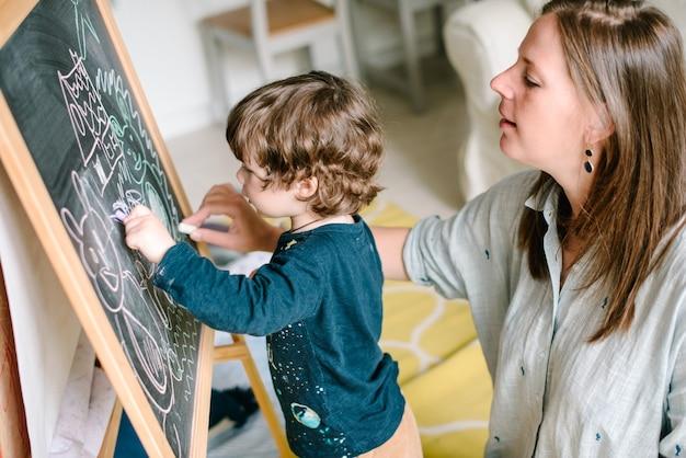 집에서 그의 어린 아들과 함께 칠판에 분필을 그리는 젊은 어머니