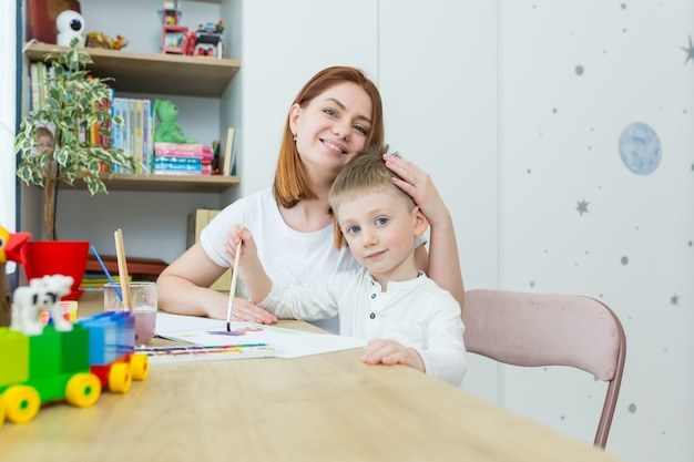 Young mother draws teaches her little son to draw, in the nursery at home, having fun together