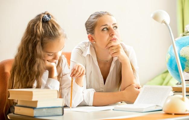 娘が宿題をしている間に夢を見る若い母親