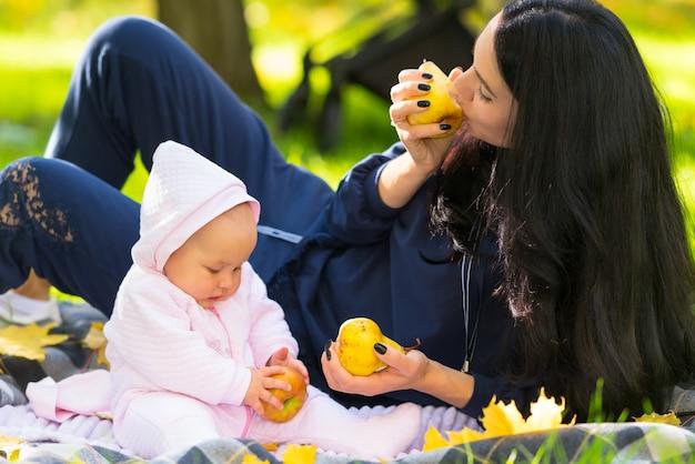 그들은 공원에서 담요에 함께 휴식으로 그녀의 아기 딸과 함께 가을 사과를 먹는 젊은 어머니
