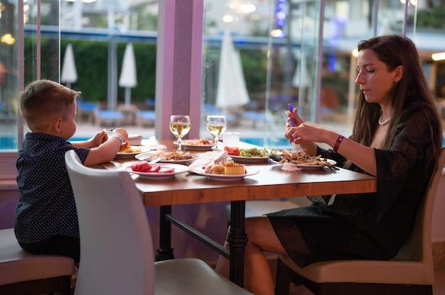 若い母親はレストランで子供と一緒に食事をします。
