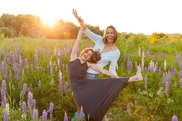 Молодая мать, обнимая своего ребенка на открытом воздухе. женщина и девочка-подросток на летнем поле с цветущими полевыми цветами зеленом фоне