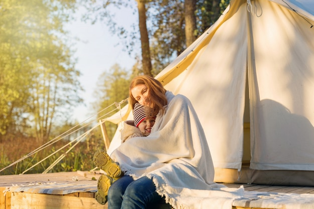 Young mother embracing her happy kid with a blanket while sitting near canvas bell tent in the forest