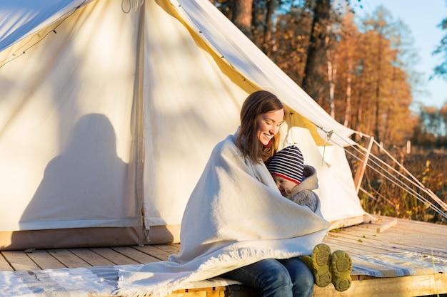 캔버스 벨 텐트 근처에 앉아있는 동안 담요로 그녀의 작은 아이를 껴안은 젊은 어머니
