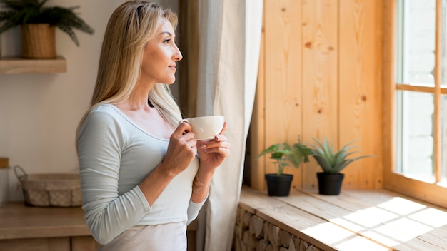 Young mother enjoying a cup of coffee while looking through window