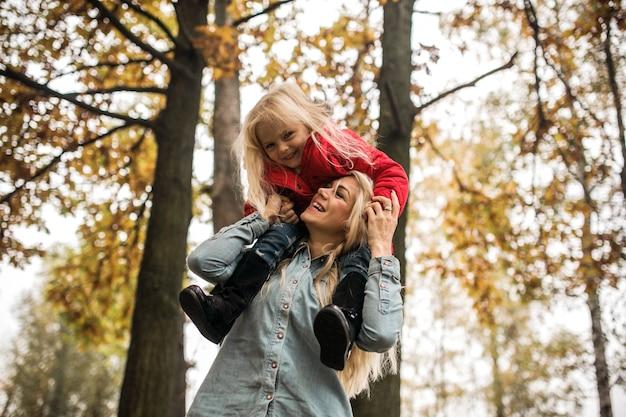 Молодая мать, наслаждаясь с дочерью на открытом воздухе
