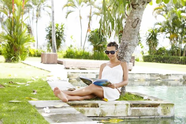 Молодая мать в солнцезащитных очках отдыхает под деревом с журналом в руках во время отпуска в тропической стране.