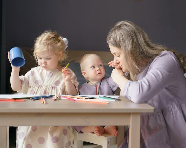 Молодая мать выражает любовь маленькому сыну, играя с детьми дома