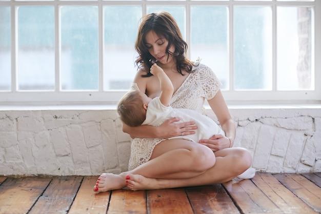 白い部屋で自宅で赤ちゃんを授乳する若い母親