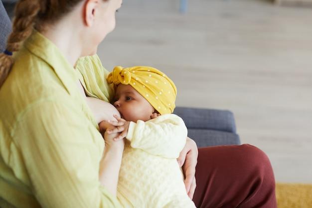 Молодая мать кормит грудью новорожденного ребенка, сидя на диване в комнате