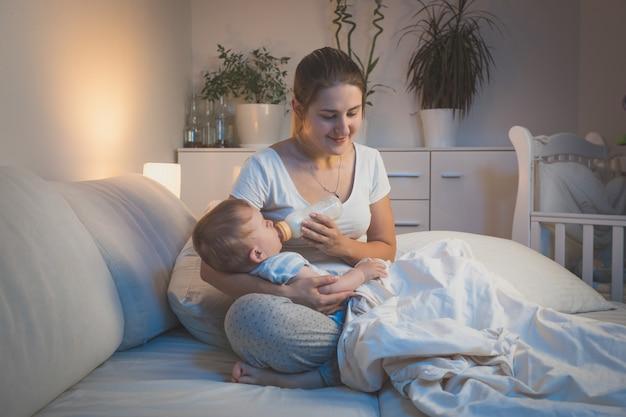 哺乳瓶から夜に赤ちゃんを養う若い母親