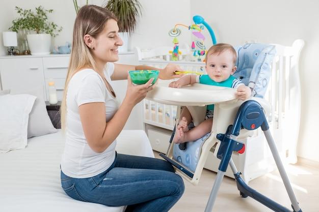 Молодая мать кормит своего мальчика фруктовым соусом в высоком стульчике