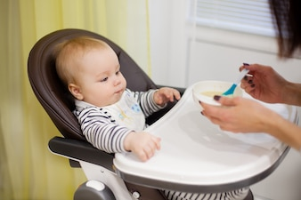 Young mother feeding her little baby son with porridge,who sitting in high baby chair