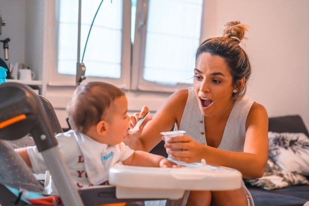 Young mother feeding her son a yogurt while sitting in the highchair