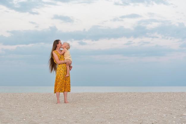 若い母親は娘を優しく抱きしめてキスします。海の背景にママと赤ちゃん。