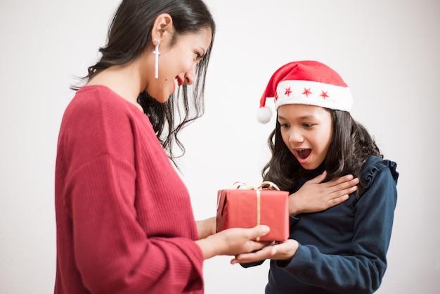 젊은 어머니는 흰색 바탕에 그녀의 딸에 게 크리스마스를위한 빨간색 예쁜 선물을 제공합니다.