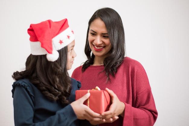 산타 모자를 쓰고 딸에게 선물을주는 젊은 어머니.