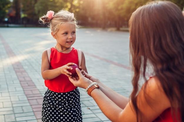 小学校の屋外で娘にリンゴを与える若い母親。レッスンの準備ができている小さな生徒。教育