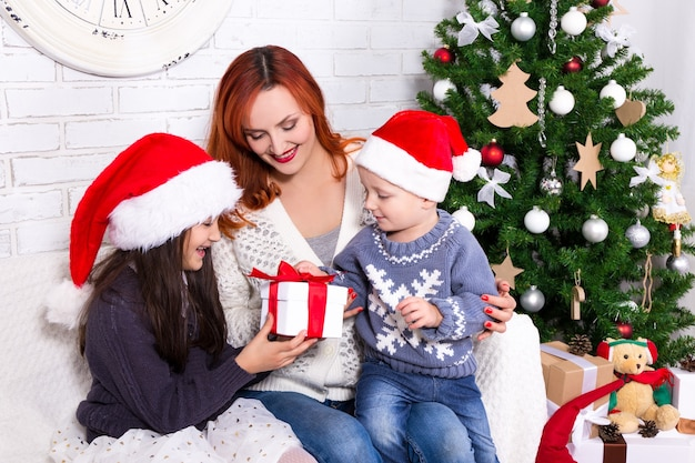 Young mother giving presents to her kids in front of christmas tree