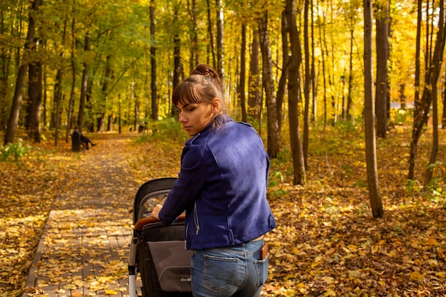 Young mother goes with a stroller in the autumn park a oneyearold infant is sleeping in a carriage