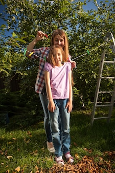 Young mother hanging daughter on string with clothespin