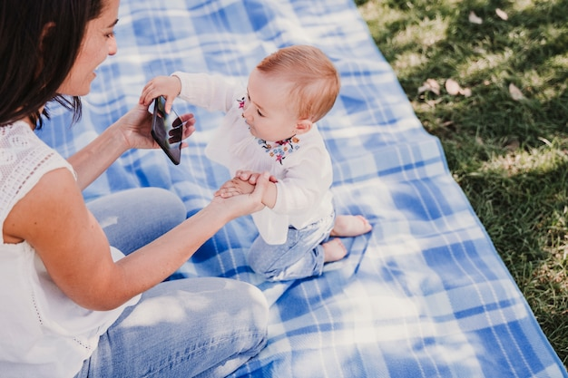 Young mother and happy baby using mobile phone outdoors. technology concept