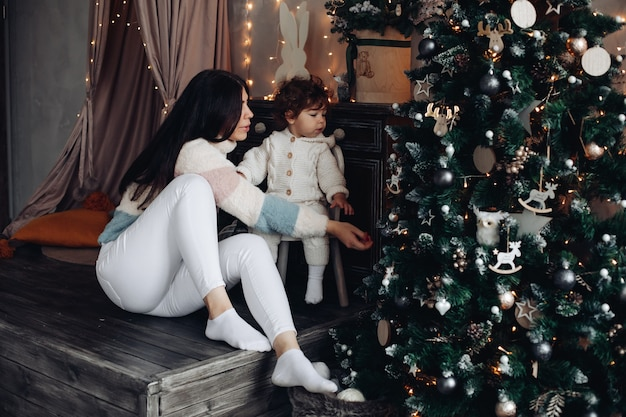 Young mother has a lot of fun with her baby near the christmas tree at home