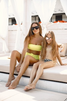 若い母親は子供と一緒に休暇をとっています。どちらも柔らかいサンベッドに座ってカクテルを飲みながら水着を着ています。夏休みのコンセプト、家族関係。ヨーロッパ人。