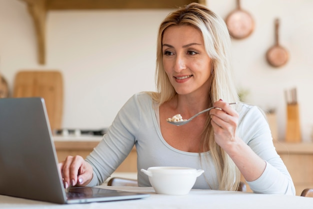 Young mother having breakfast and working from home