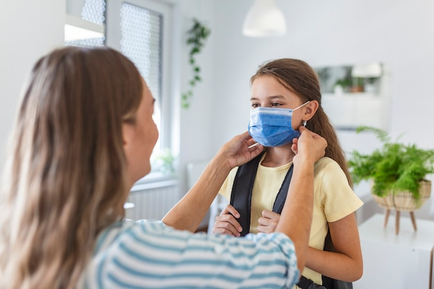 若い母親は、娘が学校に行く準備をするために医療用マスクを着用するのを手伝っています。 covid-19またはコロナウイルスの発生を回避します。学校に戻る