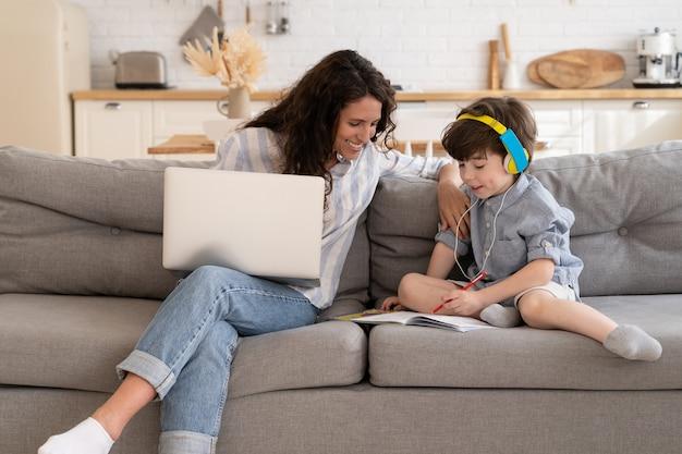 젊은 어머니는 집에서 랩톱 컴퓨터에서 원격으로 일하는 동안 오디오 수업 숙제로 아이를 돕습니다.