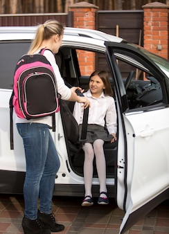 Young mother helping daughter to get inside the car after school lessons