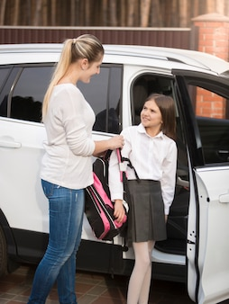 Young mother helping daughter to get out of car and put on school bag