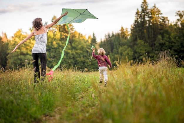 Young mother helping her child to fly a kite as he runs through an autumn grassland