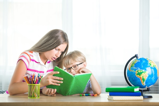Young mother helping her child to study at home. cute little boy reading a textbook with his mom on neutral background.