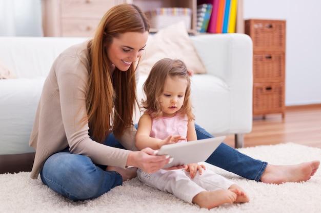Молодая мать помогает дочери с цифровым планшетом