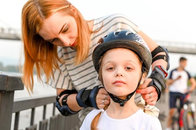 若い母親は、幼い娘が自転車のヘルメットをかぶるのを手伝っています。母親と活発な散歩をしている就学前の女の子