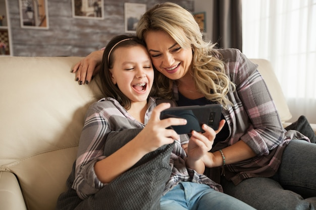 若い母親は、アパートのソファに座っているスマートフォンからアプリを使用するために、中かっこで幼い娘を助けています。