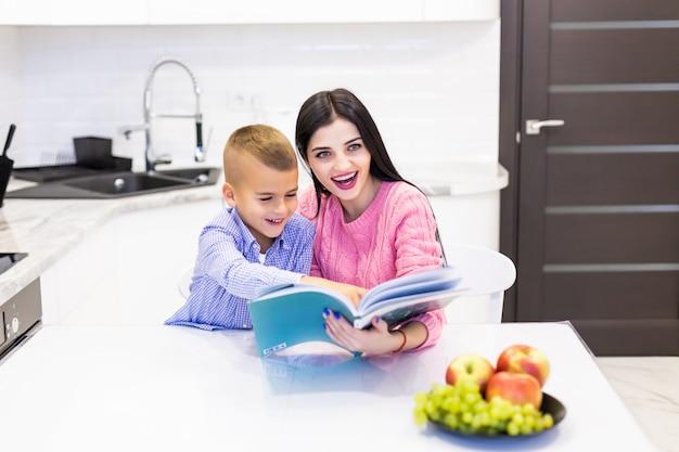 若い母親が息子が家庭の台所で宿題をするのを手伝う