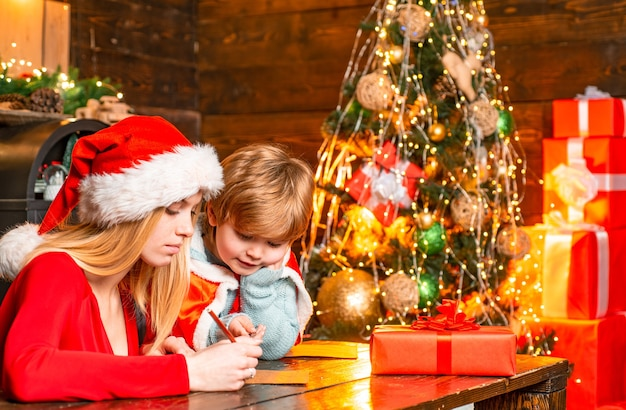 彼女の息子がサンタの冬休みと子供の頃のコンセプトのクリスマスツリーに手紙を書くのを手伝っている若い母親...