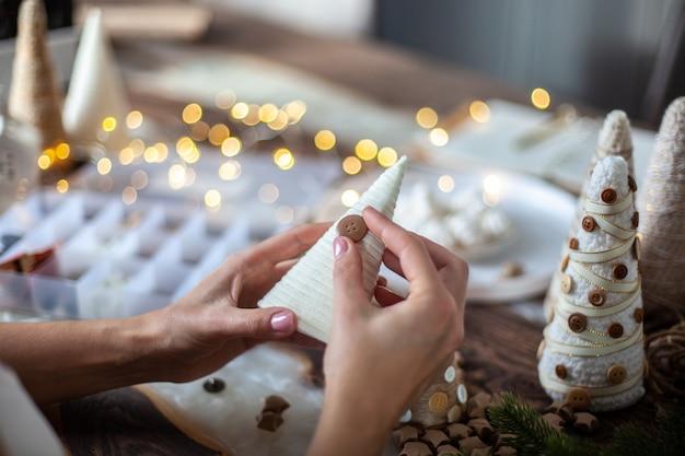 若い母親は、フォームコーンを紐や毛糸で包み、テーブルの装飾用にさまざまなサイズのクリスマスツリーを作るために娘を助けています。ホリデーシーズンとパーティーの準備のコンセプト。