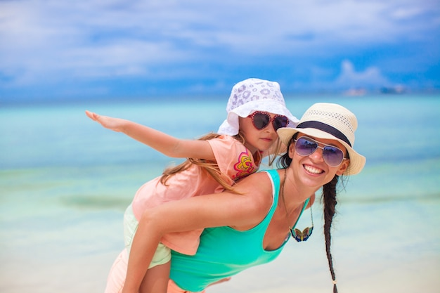 Young mother and her adorable little daughter have fun at tropical beach