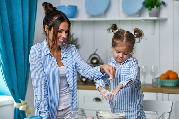 Young mother and her beautiful daughter knead dough in the kitchen