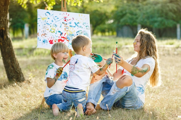 Young mother and her child drawing at each other. happy family outdoors